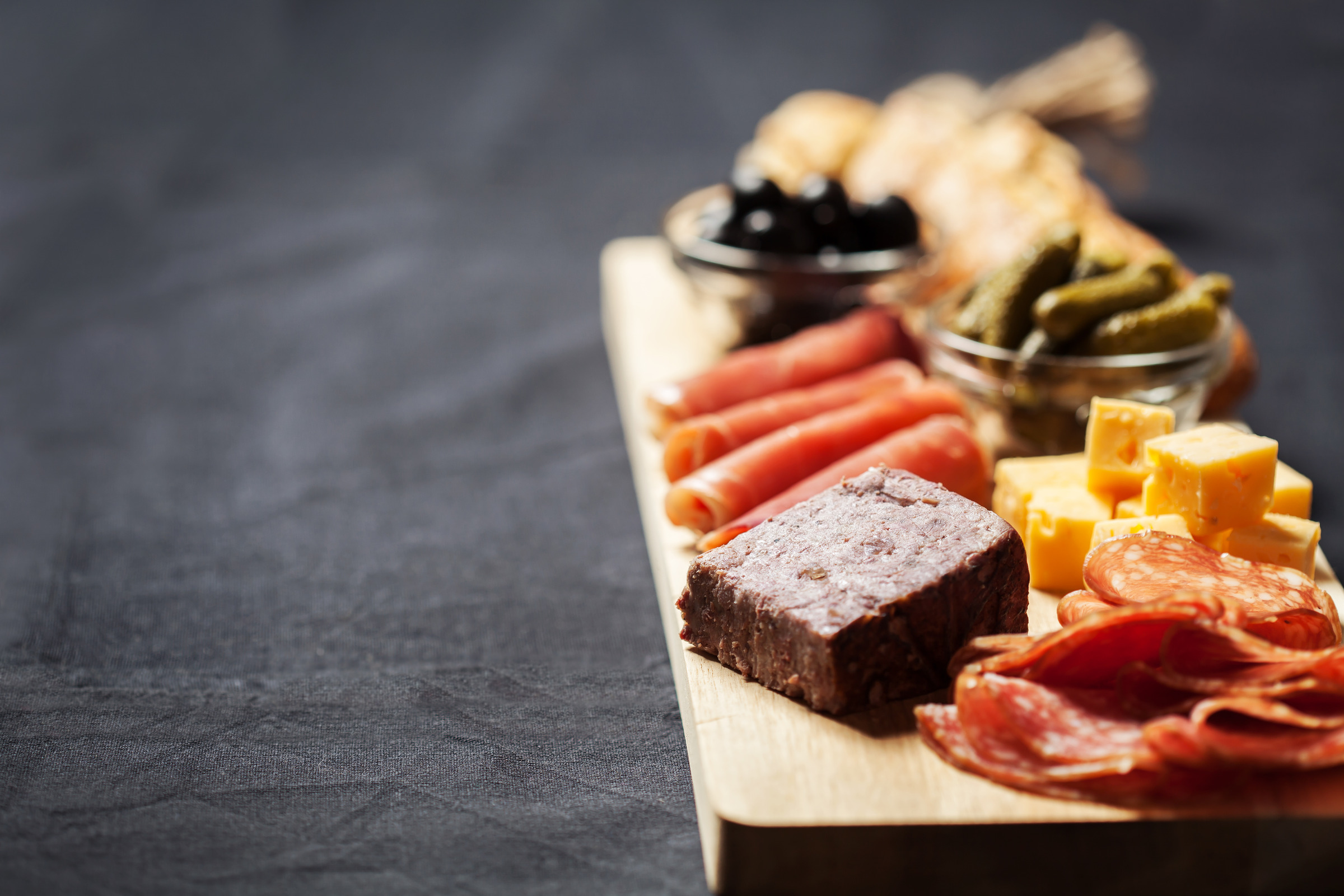 Charcuterie assortment, cheese, olives and gherkins on wooden board