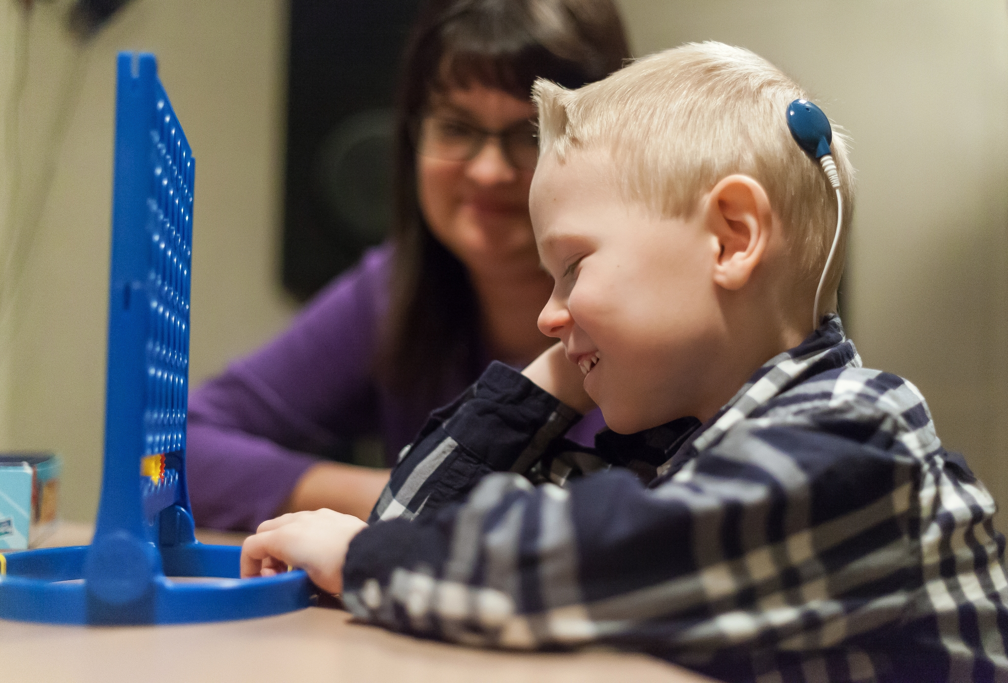 Child audiology patient playing connect four with Glenrose staff.
