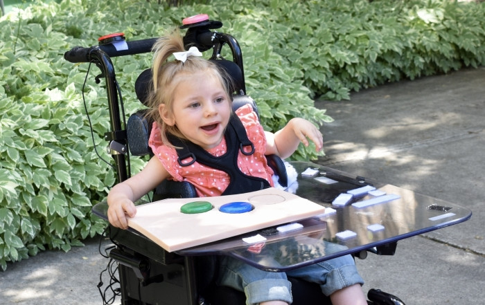 Patient Avery in her power mobility chair outside smiling.