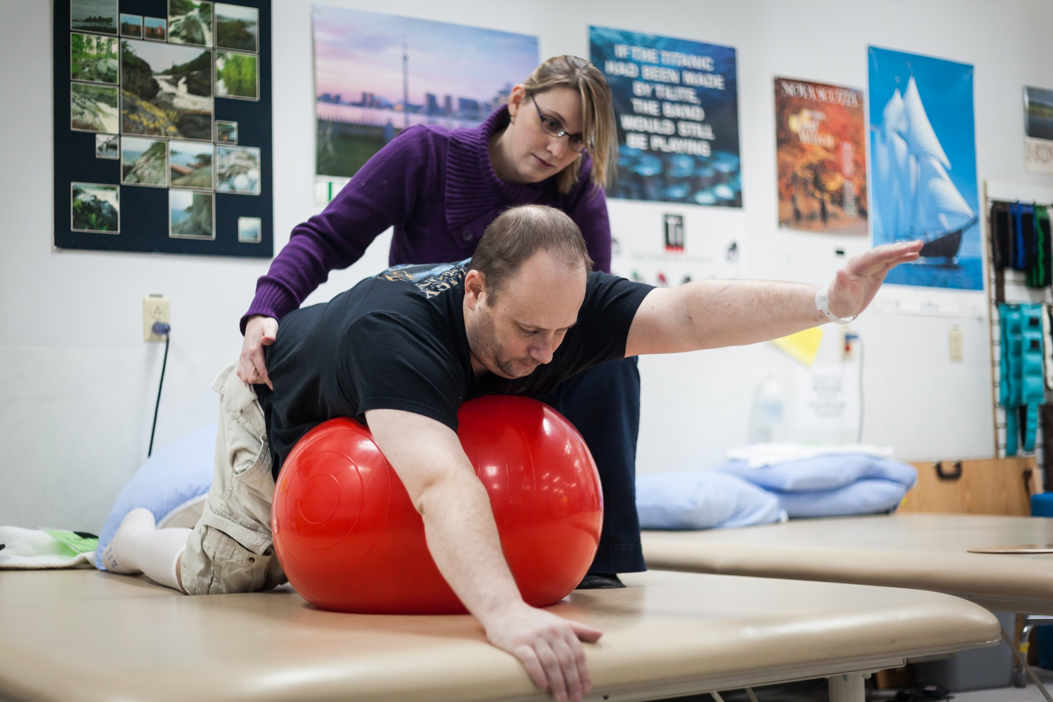 Physiotherapist working with adult patient on mobility exercises using large exercise ball.