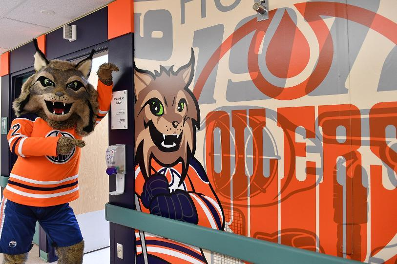 Oilers mascot Hunter standing outside a room with an oilers decal on the wall
