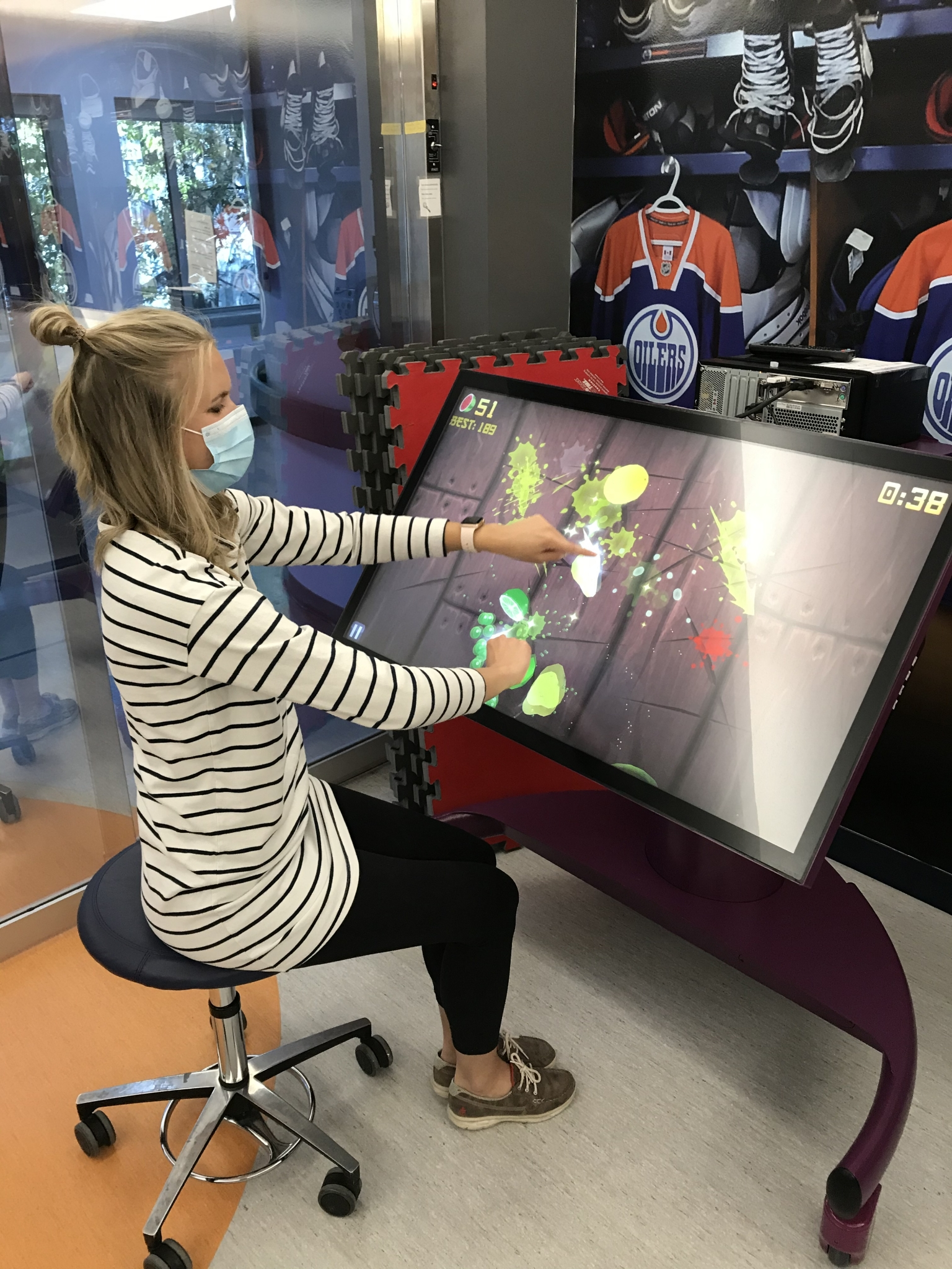 Woman seated at a large touch screen piece of equipment
