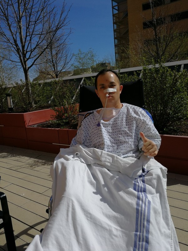 Man in a wheelchair dressed in hospital robe